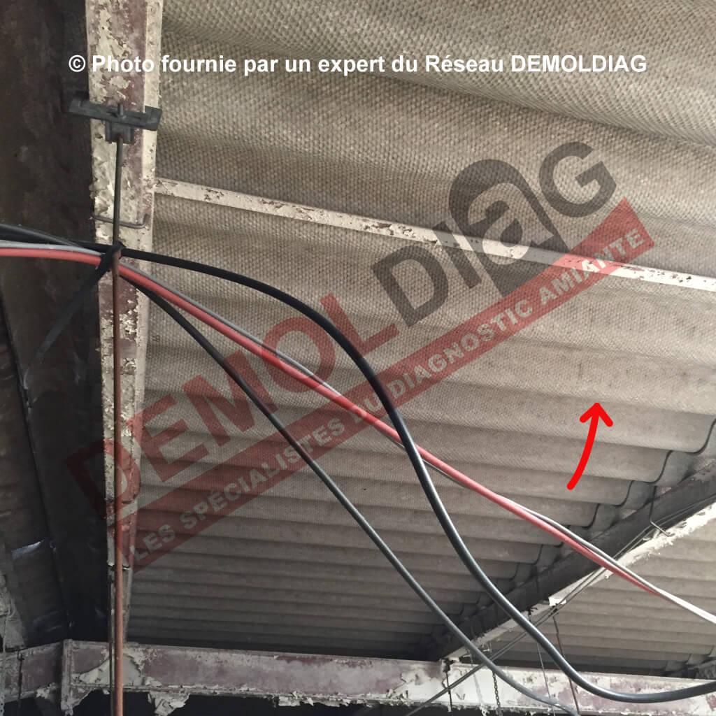 Rénovation énergétique : Sous face de toiture en panneaux d'amiante-ciment susceptible d'être impactée par les travaux d'isolation thermique réalisés dans les combles