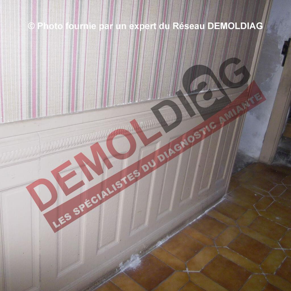 Rénovation énergétique : Parement intérieur (soubassement de mur) mouluré en panneaux d'amiante-ciment susceptible d'être impactés par des travaux d'isolation.